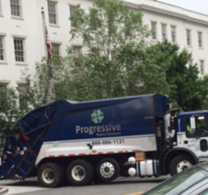 """A garbage truck bearing the name """"progressive"""" turns left as it exits Republican National Committee headquarters, June 2, 2016."""